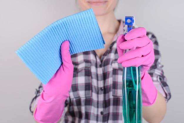 Foto de uma mulher sorridente demonstrando um frasco de spray transparente