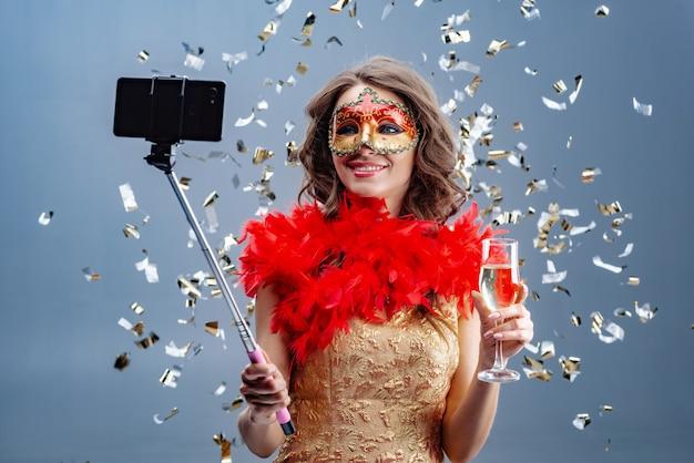 Foto de uma mulher sorridente em máscara de carnaval e vestido de ouro com vidro levantado faz selfie em um telefone móvel