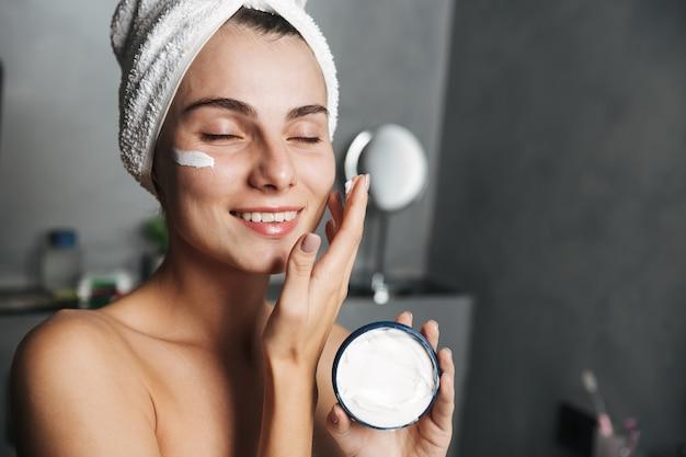 Foto de uma mulher sorridente enrolada em uma toalha, aplicando creme no rosto