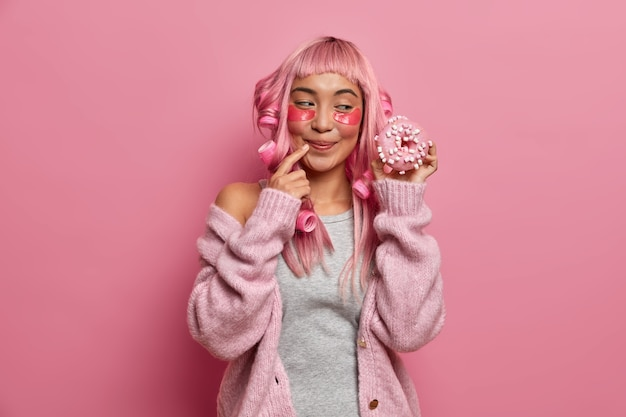 Foto de uma mulher sorridente, parecendo um goog, tem um dente doce e parece com apetite em um delicioso donut, usa rolos de cabelo, tem um penteado rosa