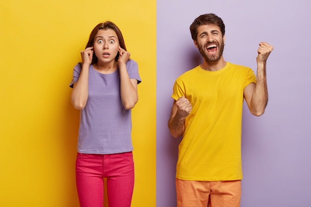Foto de uma mulher surpresa tapando os ouvidos, chocada com o barulho, e o homem cerrando os punhos