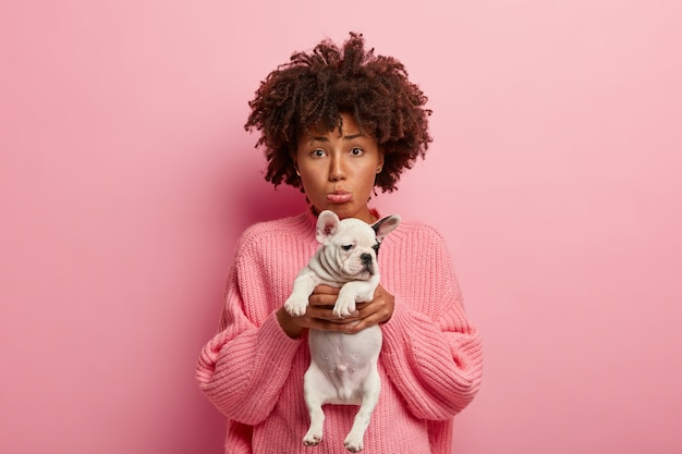 Foto de uma mulher triste e deprimida se sentindo infeliz porque seu animal de estimação está doente, leva um cachorrinho ao veterinário, franze os lábios, pede para curar o animal, usa um macacão rosa solto, posa junto com o cachorro dentro de uma parede rosada