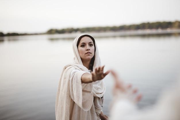 Foto de uma mulher vestindo um manto bíblico enquanto estende a mão em direção a jesus cristo