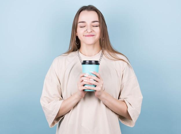Foto de uma namorada alegre e positiva segurando uma xícara de café para viagem, sorrindo com os olhos fechados, isolada em um fundo colorido brilhante