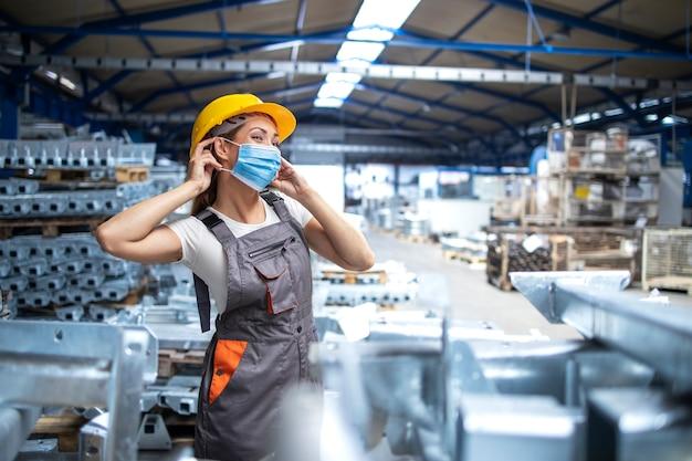 Foto de uma operária de fábrica de uniforme e capacete de segurança colocando máscara facial em uma fábrica de produção industrial