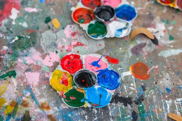 Foto de uma paleta de artistas carregada com várias tintas de cor no fundo da mesa de madeira