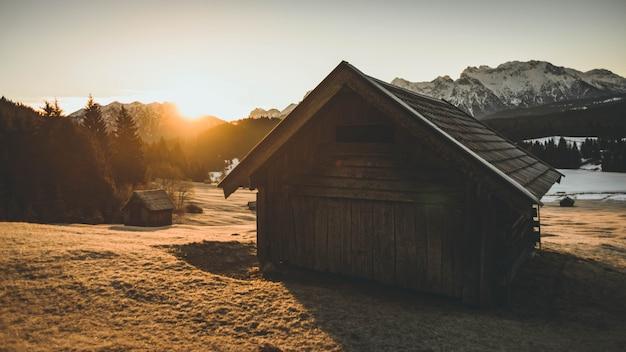 Foto de uma pequena casa de madeira com grama seca ao seu redor durante o pôr do sol com montanhas na backgro