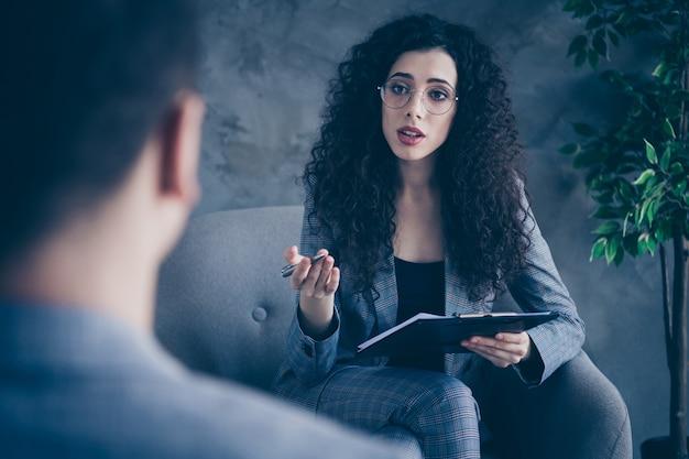 Foto de uma psicóloga sentada na cadeira, ouvindo o cliente, sobre o fundo da parede de concreto