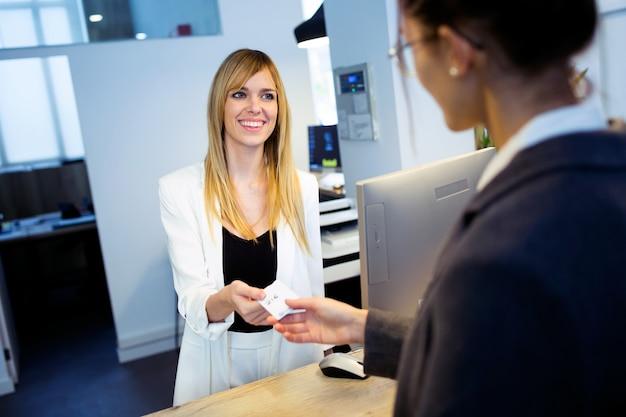 Foto de uma recepcionista atraente dando o cartão-chave do quarto para uma cliente no hotel.