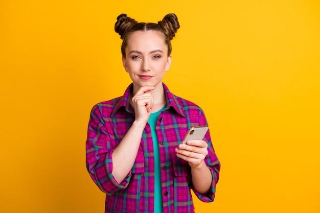 Foto de uma senhora adolescente de mente atraente segurando as mãos do telefone, blogueira, pensando em escrever um braço criativo no queixo, usar camisa xadrez magenta casual isolado fundo de cor amarela brilhante
