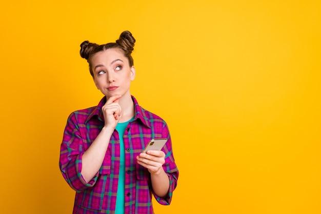 Foto de uma senhora adolescente de mente atraente segurar as mãos do telefone blogger olhar pensar no espaço vazio escrever postagem criativa vestir camisa xadrez magenta casual isolado amarelo brilhante cor de fundo