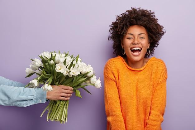 Foto de uma senhora afro-americana encantada rindo sinceramente, recebendo flores do marido ou namorado