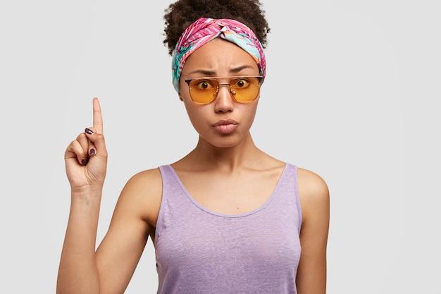 Foto de uma senhora afro-americana indignada e intrigada com expressão preocupada, aponta com o dedo indicador para cima, vestida com roupa casual, óculos de sol da moda, isolada sobre a parede branca