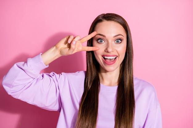 Foto de uma senhora atraente e alegre mostrando o símbolo do sinal de v com dois dedos próximo ao olho, diga oi amigos reunião reunião de festa vestir suéter roxo casual isolado fundo rosa cor pastel