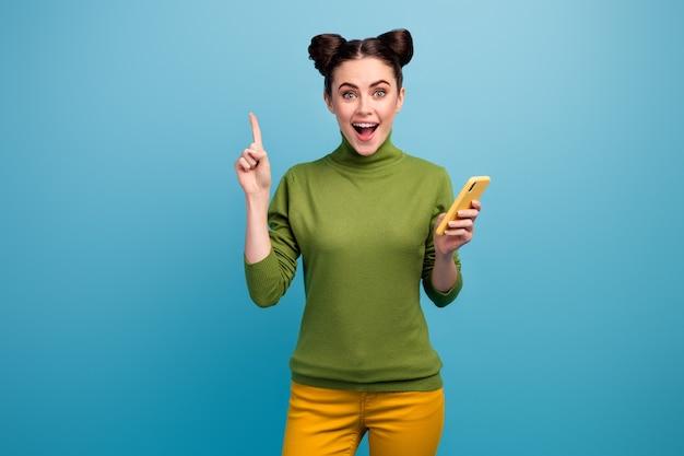 Foto de uma senhora atraente e engraçada, segurando o telefone, levantando o dedo, tem uma ideia inteligente e criativa para o novo texto da postagem do blog usar calça verde de gola alta amarela isolada na parede azul