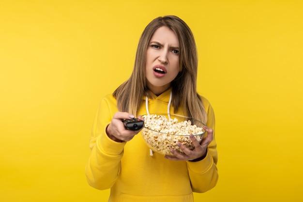 Foto de uma senhora atraente segura o controle remoto da tv e o prato de pipoca, com cara de descontente tentando mudar de canal veste casuais com capuz amarelo, fundo de cor amarela isolado.