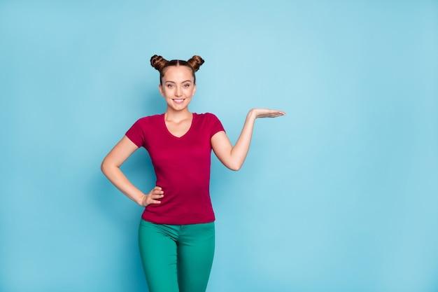 Foto de uma senhora bonita bonita e alegre em uma camiseta vermelha segurando um espaço vazio com a mão em pé com confiança com a mão na cintura segurando uma parede de cor pastel isolada de calças