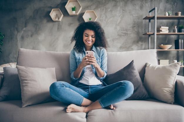 Foto de uma senhora bonita de pele morena encaracolada doméstica enviando mensagens de texto telefone com amigos lendo comentários do instagram sentados sofá confortável roupa de jeans casual sala de estar