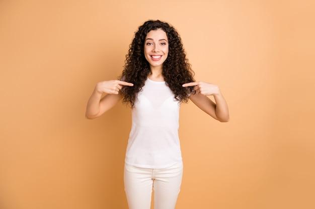 Foto de uma senhora bonita e incrível, com autoconfiança apontando os dedos no peito, anunciando sua personalidade, vestir roupa casual branca isolada fundo bege