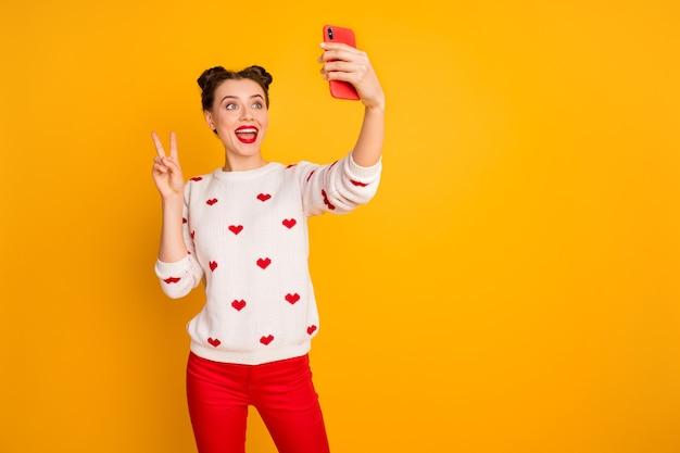 Foto de uma senhora bonita engraçada segurando as mãos do telefone tirando selfies mostrando o símbolo de um v para o blog on-line usar corações com padrão de suéter branco