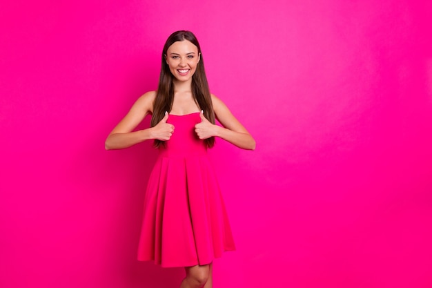 Foto de uma senhora bonita levantando o polegar aprovando a boa qualidade dos produtos. use um vestido brilhante e elegante e elegante com fundo de cor rosa viva