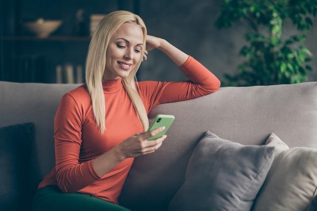 Foto de uma senhora bonita loira caseira, humor doméstico, trocando mensagens de texto com amigos de telefone lendo, assistindo a postagem no instagram, sentada em um sofá confortável, roupa casual, sala de estar dentro de casa