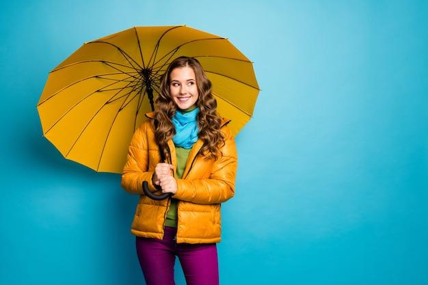 Foto de uma senhora bonita, olhar ao lado, espaço vazio segurar grande guarda-chuva aberto, desfrutar de um dia ensolarado, caminhar pela rua, usar sobretudo amarelo, lenço azul, calças violeta, parede de cor azul isolada