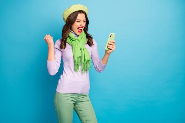 Foto de uma senhora bonita segurando as mãos do telefone lendo novas reações de comentários positivos usando boina verde, calça cachecol de gola alta roxa, parede de cor azul isolada
