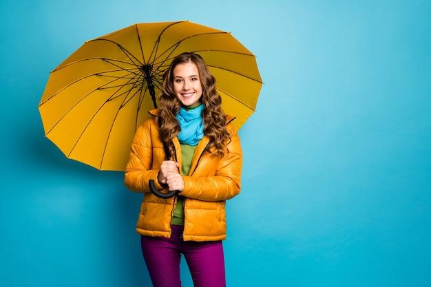 Foto de uma senhora bonita segurando guarda-chuva brilhante desfrute de um dia ensolarado, caminhada pela rua, bom humor, usar sobretudo amarelo, lenço azul, calças violeta, parede de cor azul isolada