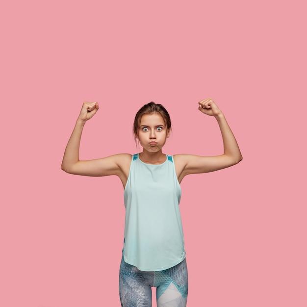 Foto de uma senhora caucasiana de olhos arregalados assoando as bochechas, levantando as mãos, mostrando força