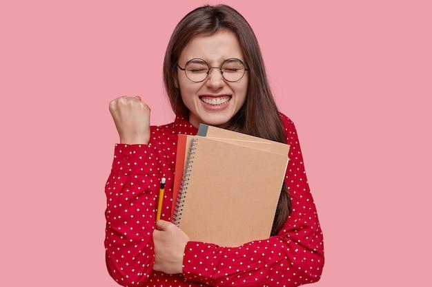 Foto de uma senhora caucasiana muito feliz com o punho cerrado, com um largo sorriso, segurando um bloco de notas, um lápis, aplaude quando tem sucesso