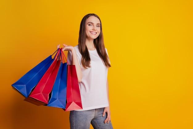 Foto de uma senhora compradora segurando pacotes usando camiseta branca posando em fundo amarelo