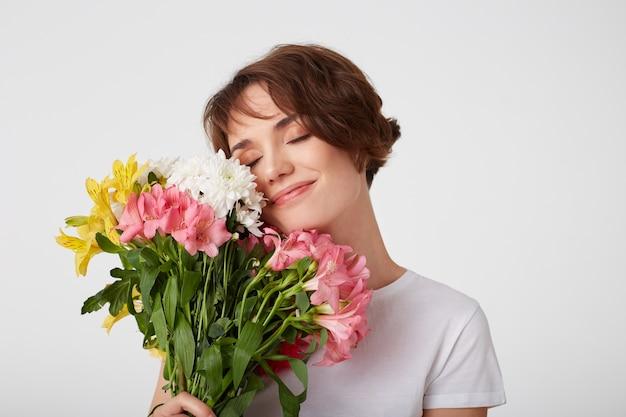 Foto de uma senhora de cabelo curto bonita em uma camiseta branca em branco, segurando um buquê, cobre o rosto com flores, apreciando o cheiro, em pé sobre um fundo branco com os olhos fechados.