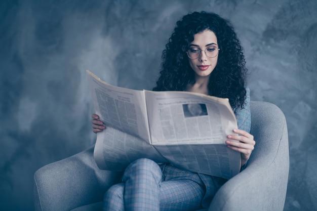 Foto de uma senhora de negócios sentada na cadeira lendo um resumo das notícias isoladas sobre a parede de concreto