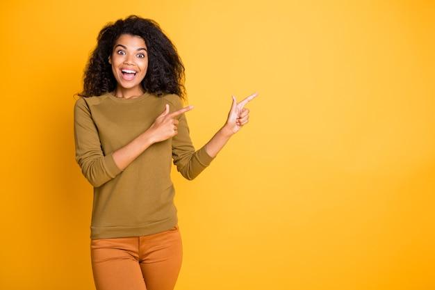 Foto de uma senhora de pele escura muito incrível, indicando o espaço vazio com os dedos, propondo preços de compra e venda, use calças casuais com fundo amarelo isolado