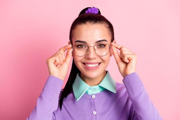 Foto de uma senhora encantadora com aparência de câmera, sorriso dentuço, tirar os óculos, usar especificações cardigan violeta fundo de cor rosa isolado