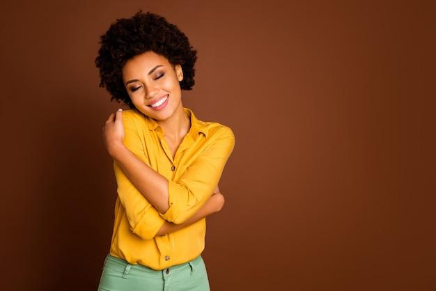 Foto de uma senhora encantadora de pele escura segurando os ombros com os olhos fechados, divirta-se, ame-se, blusa bonita, roupas, camisa amarela, calça verde