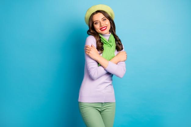 Foto de uma senhora encantadora se abraçando e curtindo a harmonia. sorridente roupas quentes usar boina verde, chapéu jumper roxo, calça cachecol, parede de cor azul isolada
