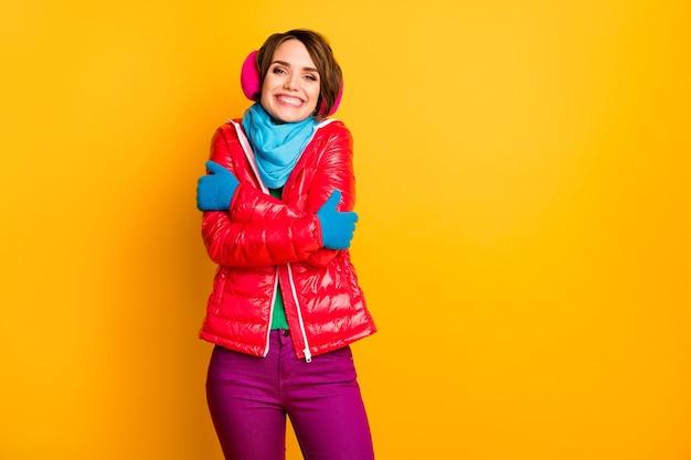 Foto de uma senhora engraçada e alegre curtindo um casaco quente em um clima frio abraça a si mesma usando um casaco vermelho curto casual, lenço azul, luvas, protetores de ouvido, calças