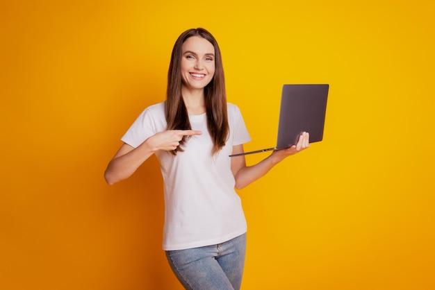 Foto de uma senhora freelancer segurando o dedo direto do laptop promovendo uma camiseta branca posando em um fundo amarelo