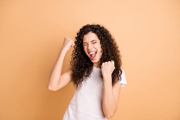 Foto de uma senhora gritando incrível ouvindo grande venda de publicidade compras triunfando levantando os punhos e vestindo roupas casuais brancas isolado fundo bege cor pastel