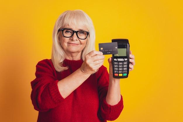 Foto de uma senhora idosa encantadora segurando o conceito de pagamento de terminal sem fio de cartão de crédito