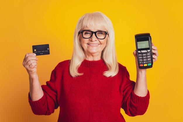 Foto de uma senhora idosa encantadora segurando um cartão de crédito terminal sem fio paypass