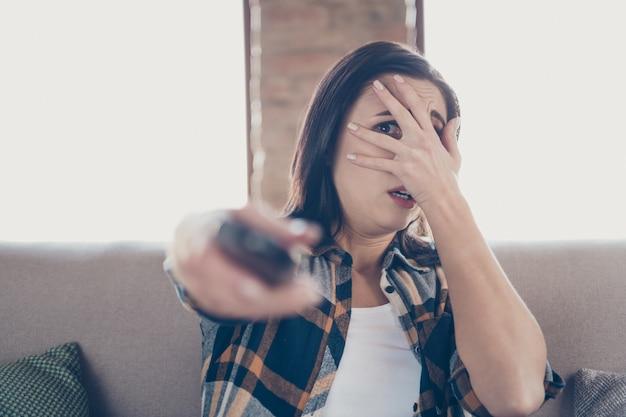 Foto de uma senhora incrível segurando o controle remoto e escondendo a expressão facial com medo de um filme de terror sentado em um sofá confortável vestindo roupas casuais apartamento dentro de casa