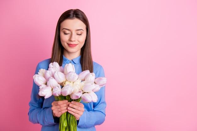 Foto de uma senhora incrível segurando um grande buquê de tulipas brancas frescas