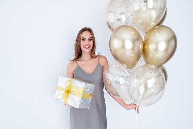 Foto de uma senhora incrível segurando uma grande caixa de presente embrulhada e muitos balões de ar que vieram para a celebração da festa