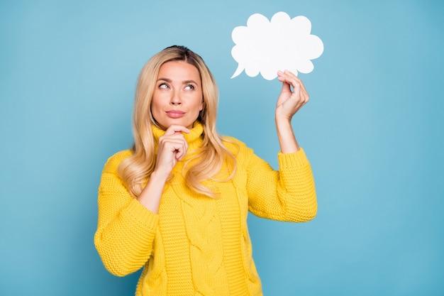 Foto de uma senhora loira incrível segurando uma nuvem mental de papel pensando sobre um diálogo criativo, resposta, mão no queixo, usar uma parede de cor azul isolada de pulôver amarelo de malha