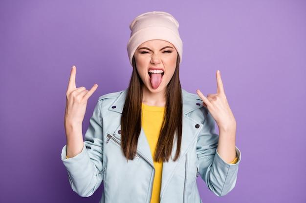 Foto de uma senhora louca e divertida mostrando a língua para fora da boca provocando comportamento roqueiro mostrando chifres mãos usar chapéu casual azul jaqueta moderna isolada fundo de cor roxa