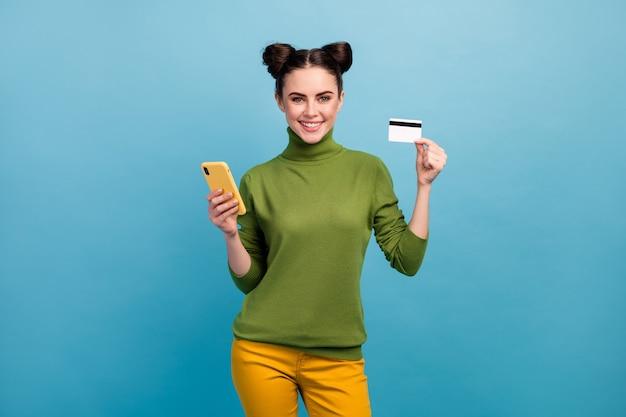 Foto de uma senhora milenar bonita segurar telefone plástico cartão de crédito aconselhando serviço legal pagamento on-line comprar usar verde de gola alta calça amarela isolada cor azul