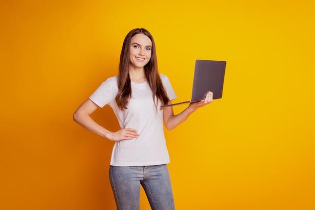 Foto de uma senhora programadora segurando um netbook com um sorriso radiante e vestindo uma camiseta branca posando em um fundo amarelo